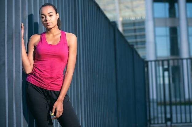 灰色のスレートフェンスの近くに立っているスポーティな服を着た思いやりのある若い女性。ウェブサイトのバナー