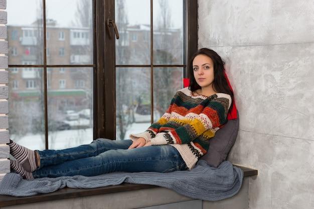 窓辺の枕の上に横になってカメラを見ている暖かいニットのセーターを着た思いやりのある若い女性