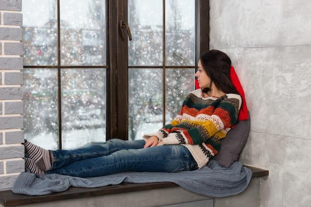窓辺の枕の上に横になり、雪が降っている間窓の外を見ている暖かいニットのセーターを着た思いやりのある若い女性