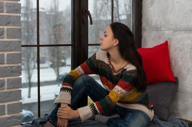 窓辺に座って窓の外を見ている暖かいニットのセーターを着た思いやりのある若い女性