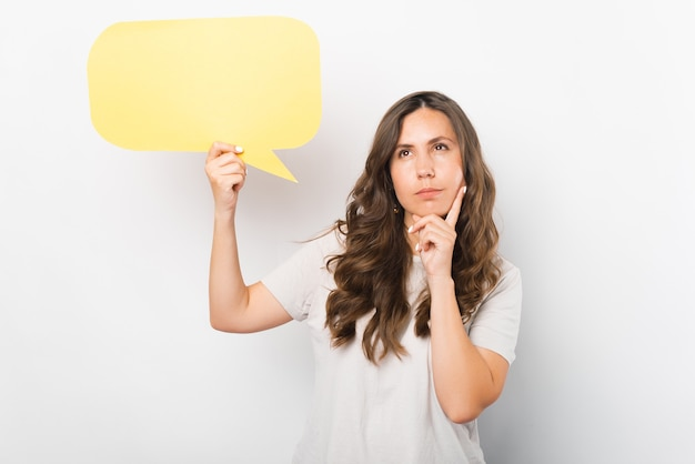 Thoughtful young woman is holding a yellow speech bubble.