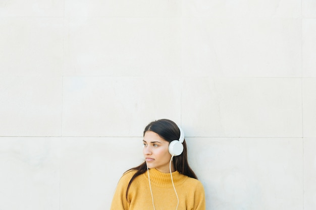 Thoughtful young woman listening music standing against white wall