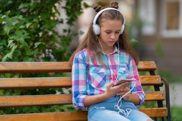 Задумчивая молодая женщина выбирает новый саундтрек на своем мобильном телефоне, сидя на скамейке под открытым небом и слушает музыку