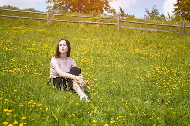 思いやりのある若い女性は花の牧草地に座っています
