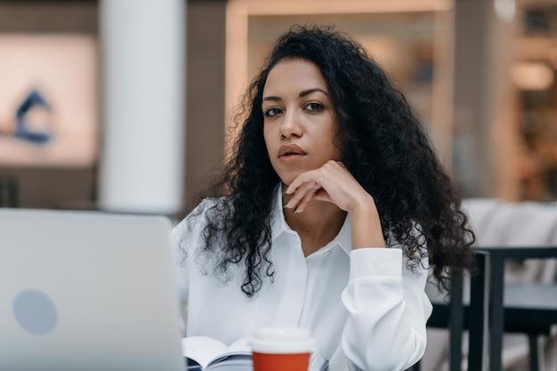 Задумчивая молодая женщина, сидящая перед открытым ноутбуком в фуд-корте