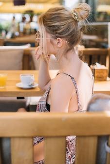 Задумчивый молодая женщина, сидя в кафе
