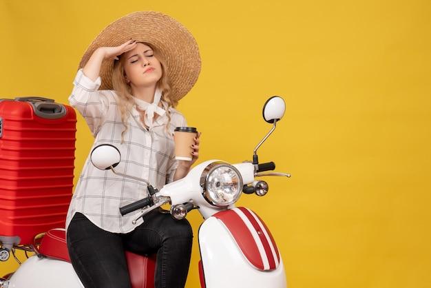 バイクに座ってチケットを見せて荷物を集める帽子をかぶった思いやりのある若い女性