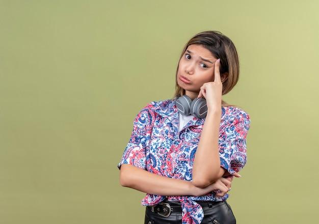 Una giovane donna premurosa che indossa la camicia stampata paisley nel pensiero delle cuffie