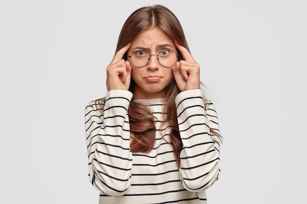 記憶力の悪い思いやりのある若い女性は、寺院に指を置き、不満な表情をしており、白い壁に隔離された縞模様のカジュアルセーターを着ています。人と思考の概念。
