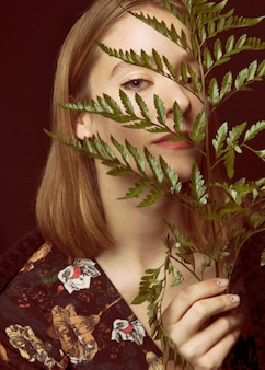 Thoughtful young woman with green plant branch