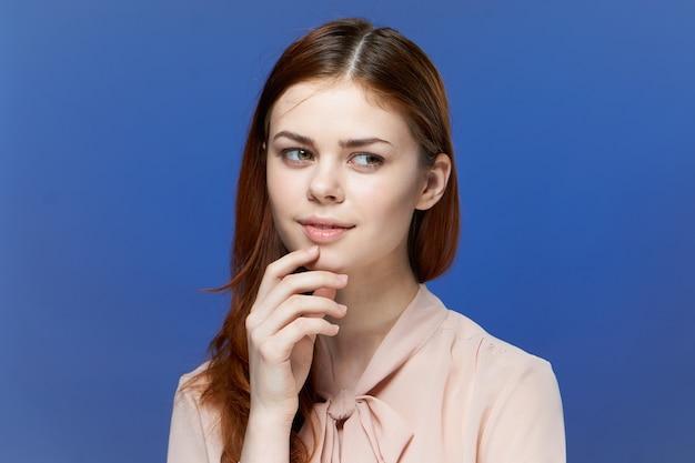 Задумчивая молодая женщина с рукой на подбородке