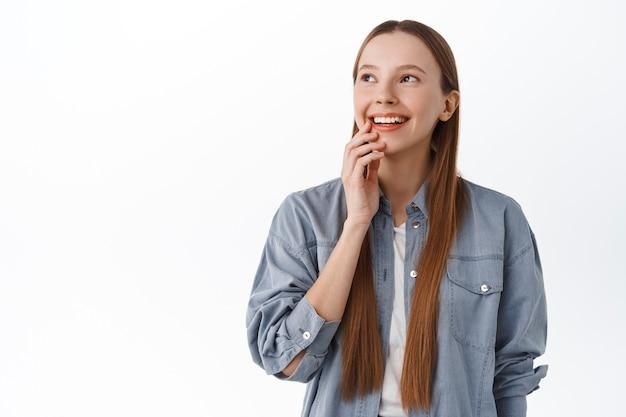 長い髪の思考、幸せな笑顔、コピースペースのプロモーションテキストを脇に見て、何かをイメージし、白い壁に立っている思いやりのある若い女性
