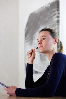 Thoughtful young woman with pen and notepad
