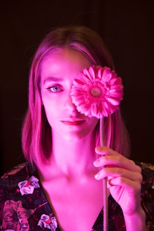 Thoughtful young woman with pink gerbera