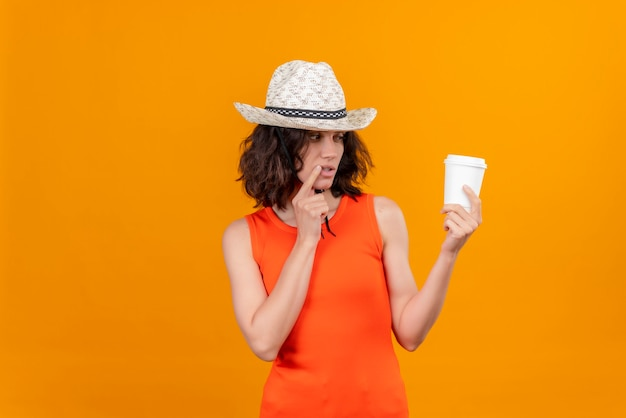 A thoughtful young woman with short hair in an orange shirt wearing sun hat looking at plastic cup