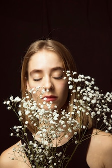 Thoughtful young woman with white flowers