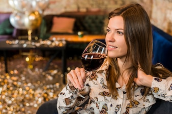 Thoughtful young woman with wine glass in bar