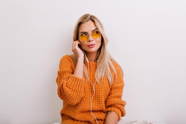 Задумчиво блондинка с большими глазами слушает музыку, сидя в своей светлой комнате