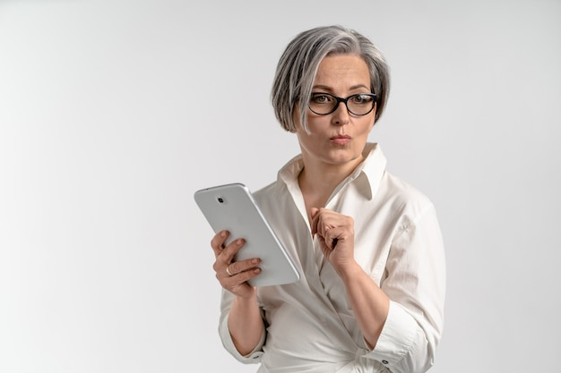 Thoughtfully businesswoman holds white tablet