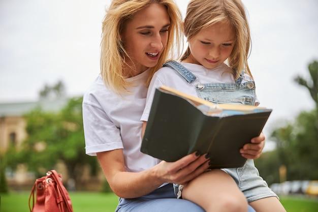 도시 공원에 앉아있는 동안 재미있는 책에서 딸과 함께 시간을 보내는 사려 깊은 어머니