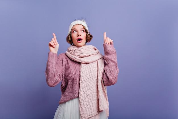 입을 벌리고 올려 귀여운 모자에 신중하게 짧은 머리 소녀. 보라색 벽에 겨울 액세서리에 포즈 평온한 여성 모델.