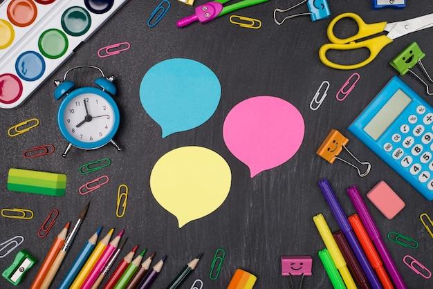 학교 개념에서의 생각과 아이디어. 칠판에 격리된 세 가지 아이디어 거품 주위에 여러 가지 빛깔의 편지지의 오버헤드 뷰 사진 위
