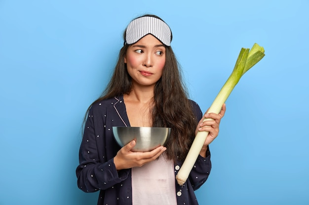 Thougtful young woman being eco friendly, holds bowl and green leek vegetable, dressed in pyjamas and sleep mask, prepares dinner for family