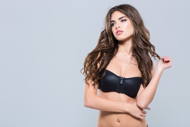 Thougthful beautiful young woman with wavy long hair in black sporty bra standing over white wall