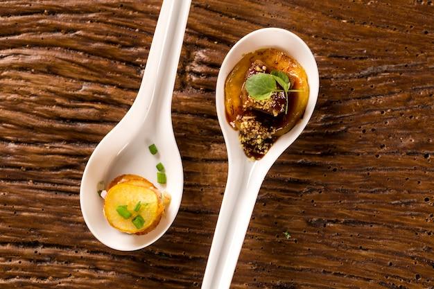 Тысячелетний сладкий картофель, свиной язык, молотый банан, измельченный марсала, водяная мука и мини-кресс-салат в ложке. вкус гастрономической еды руками