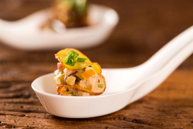 Тысячелетний сладкий картофель, копченый тунец и соленые огурцы в ложке. вкус гастрономической еды руками