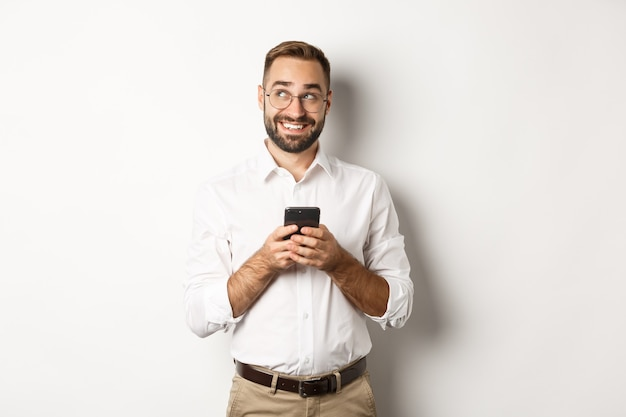 Полнотелый красивый менеджер, использующий мобильный телефон и думающий об ответе на сообщение, смотрит в левый верхний угол и улыбается, стоя