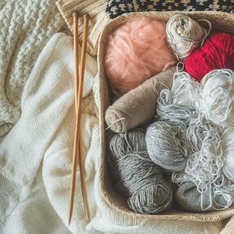 バスケットのクローズアップで編むためのスレッド。趣味の編み物。編み物用アクセサリー。