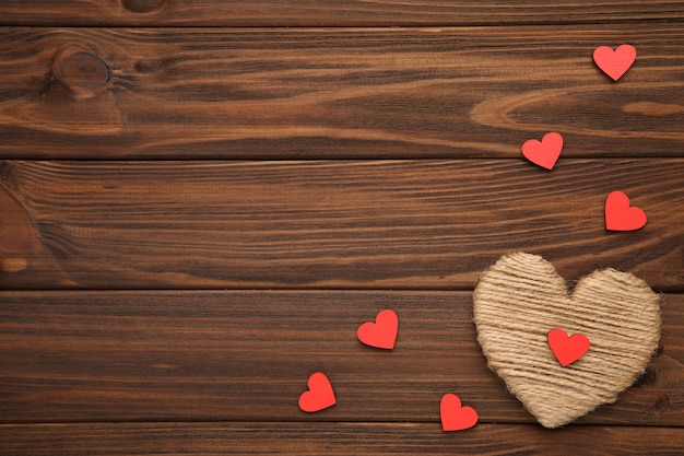 Thread heart with a wooden red hearts on a brown background