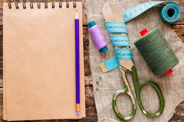 Нитка, ножницы, рулетка и блокнот для заметок на деревянной