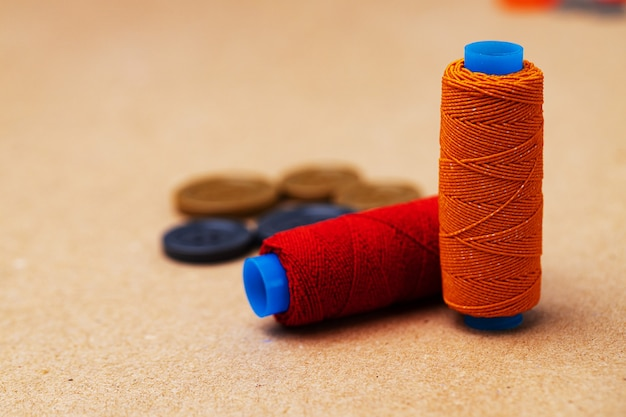 Thread spools and buttons on beige background