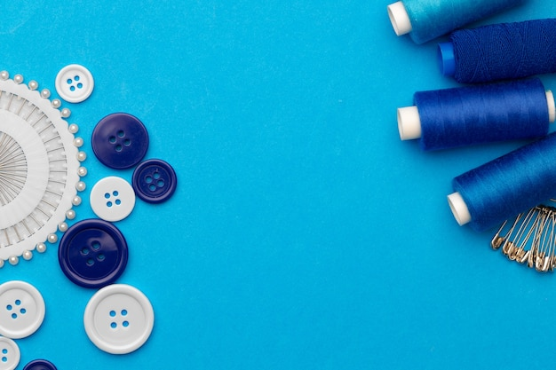 Thread spools and buttons on blue abckground