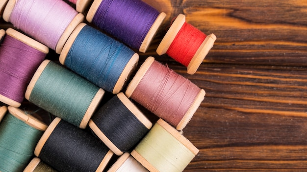 Thread spools on wood background