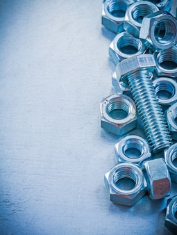 Threaded screw nuts and bolt on metallic background construction concept