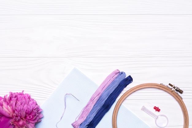 糸、刺繡のフープ、拡大鏡、牡丹の花、白の帆布
