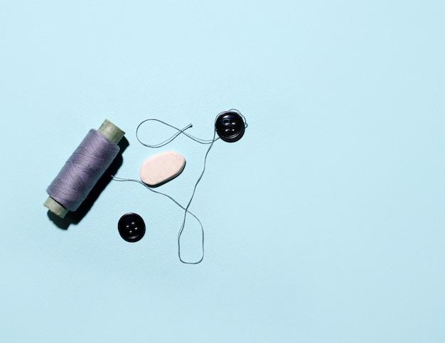青いスペースのスレッドとボタン。コピースペース。縫製のコンセプトです。ミニマリズム