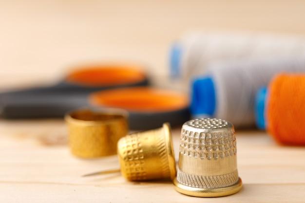 Нитки и швейные принадлежности на деревянном столе