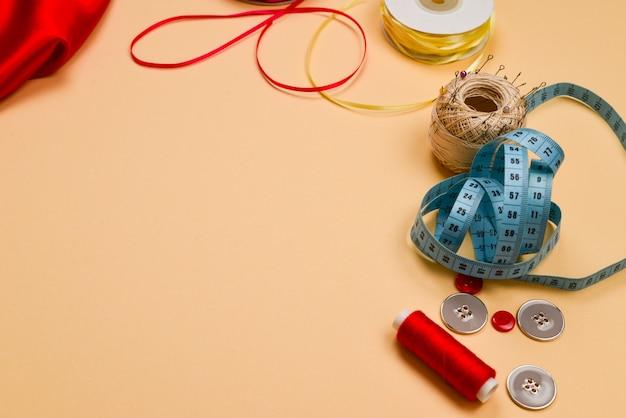 糸、ボタン、赤い布、巻尺。コピースペース。