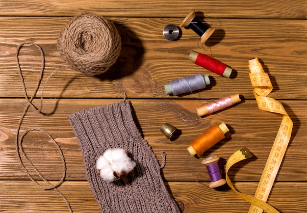 Threads and buttons and sweater sleeve on a wooden table top view. the concept of repairing and decorating old things.