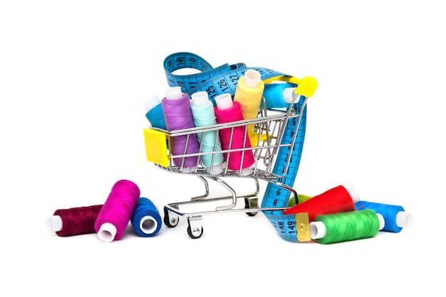 Threads of different colors are in a small cart with a tape measure.
