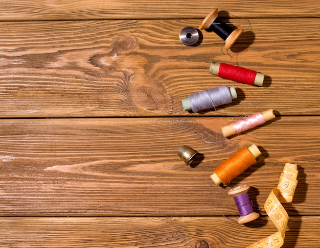 Threads of different colors on a wooden table. copy space. the concept of sewing and repairing old things
