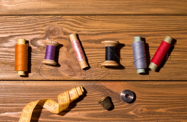 Threads of different colors on a wooden table. view from above