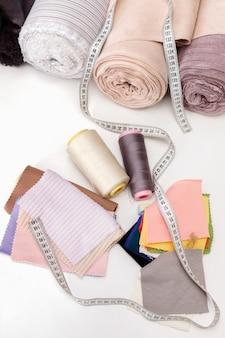 白いテーブルの上の糸、布のフラップ、センチメートルと布のロール。縫製アクセサリー