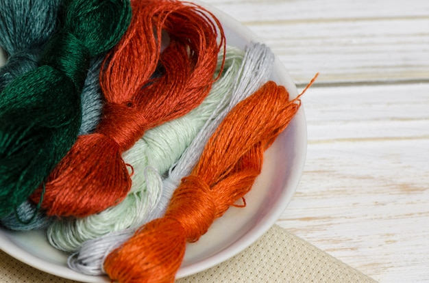 Threads for hand embroidery on wooden surface