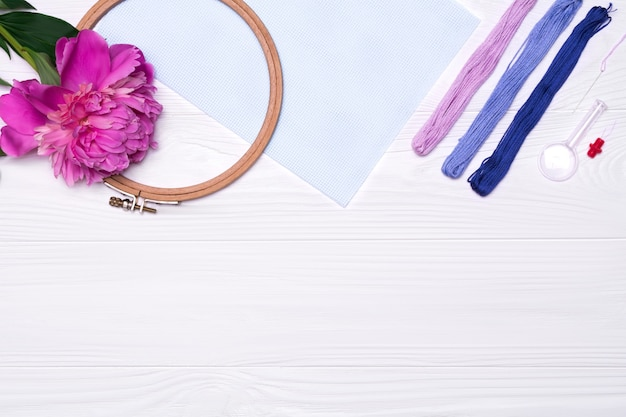 Threads, a hoop for embroidery, a magnifier, a peony flower, a canvas on white