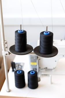 生産中のミシンの糸。ソーイングショップ。閉じる
